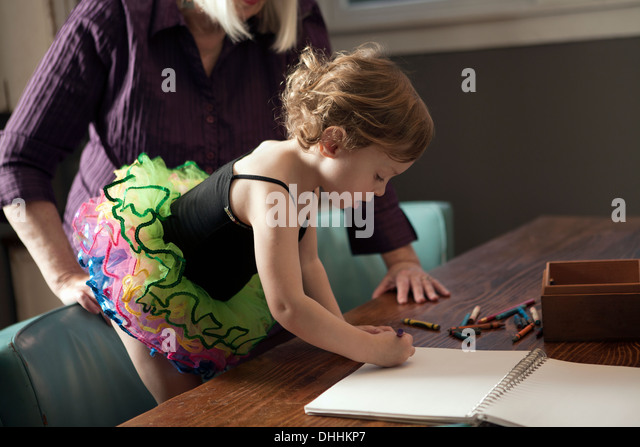 Grandmother and granddaughter standing at table drawing - Stock-Bilder