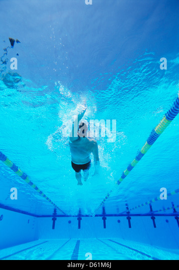 Underwater shot of young male thlete doing backstroke in swimming pool - Stock Image