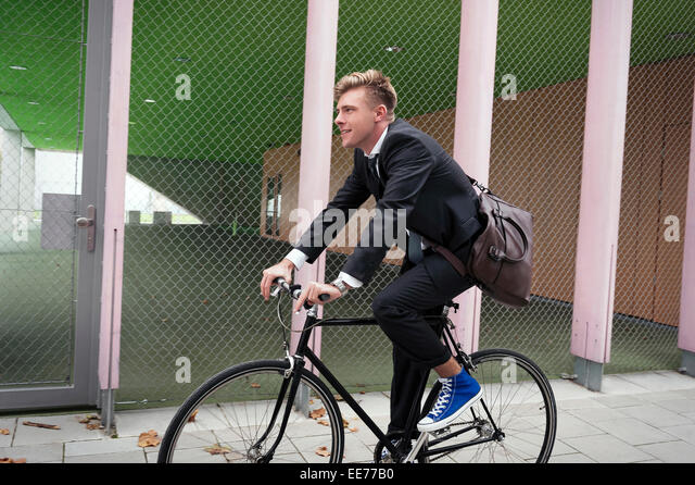 Young businessman riding bicycle, Munich, Bavaria, Germany - Stock Image