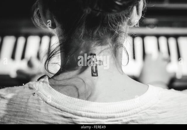 Rear View Of Woman Playing Piano With Cross On Neck - Stock-Bilder