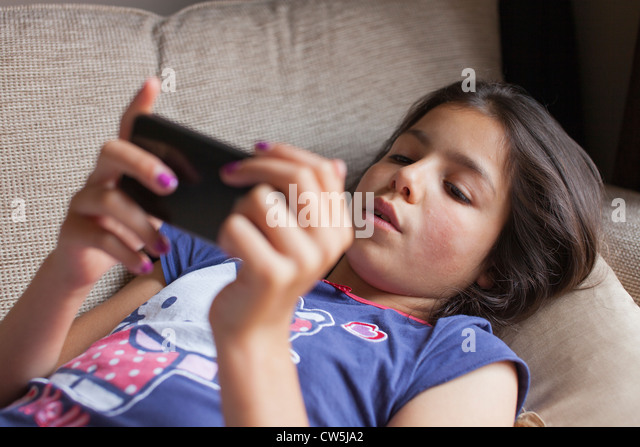 Young girl plays on mobile phone at home - Stock-Bilder