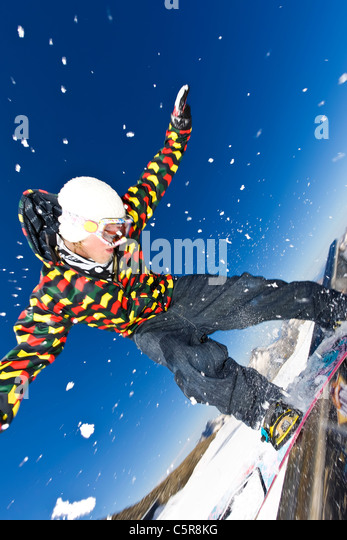 A Snowboarder balancing on a rail in a snow park. - Stock-Bilder