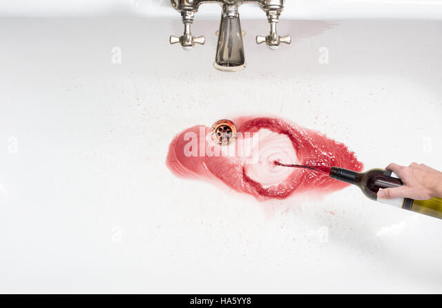Detail of a man pouring away wine in an act of giving up alcohol - Stock-Bilder