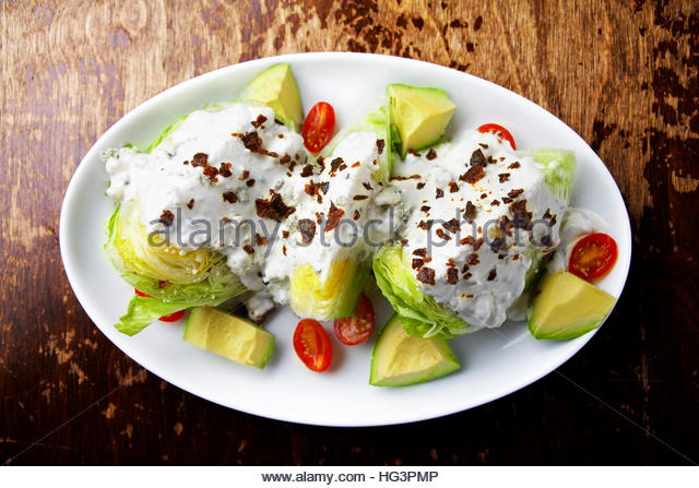 Young iceberg salad with avocado,bacon bits and, yogurt dressing - Stock Image