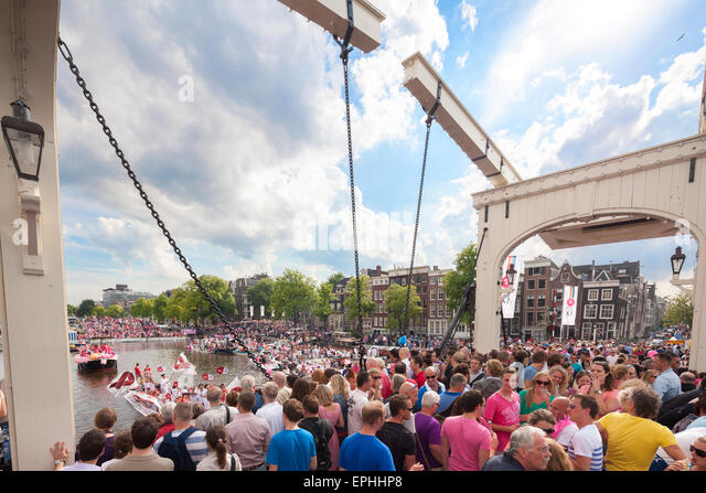 Amsterdam Gay Pride Canal Parade with crowds of visitors on the Magere Brug or Skinny Bridge on the River Amstel - Stock Image