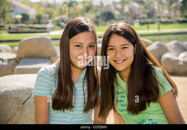 California teens hanging out Vietnamese-Caucasian and Hispanic Mexican Caucasian girls read together in park. MR - Stock-Bilder