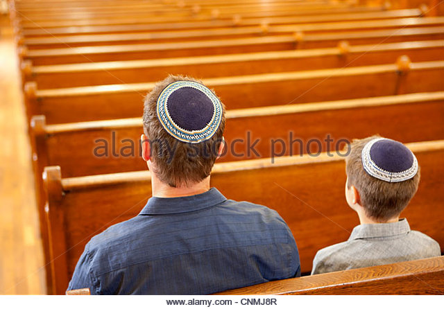 Father and son in yarmulkes sitting in synagogue - Stock-Bilder