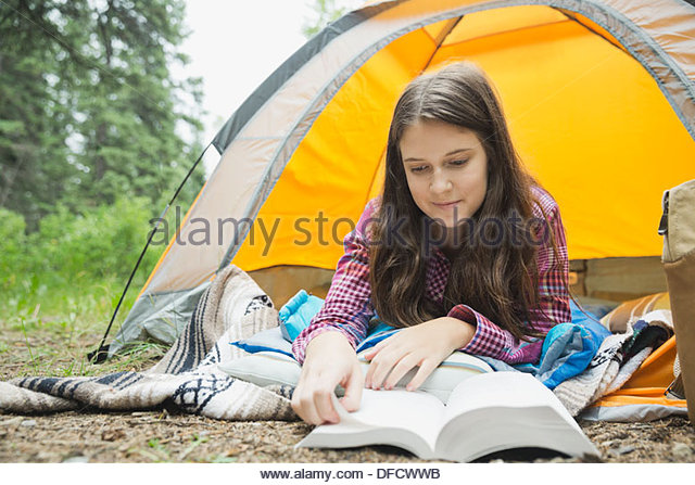 Girl reading book while lying in tent at campsite - Stock Image