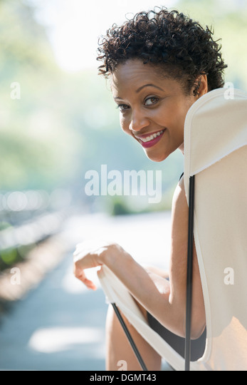 City life. A woman sitting in a camping chair in a park looking over her shoulder. - Stock Image
