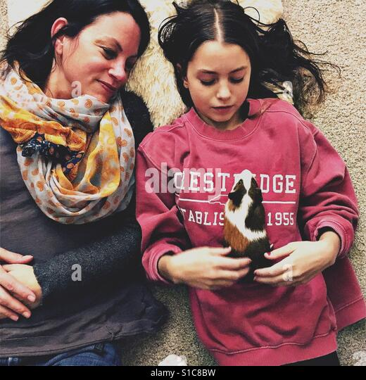 Mother and daughter with guinea pig - Stock-Bilder