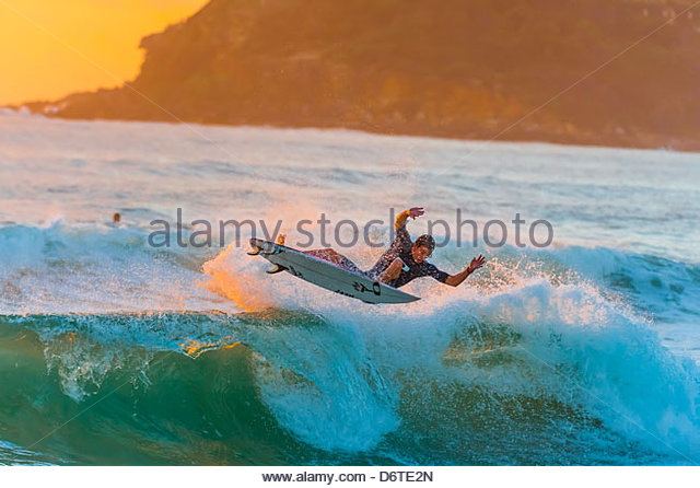 Surfing at sunrise, Manly Beach, Sydney, New South Wales, Australia - Stock Image
