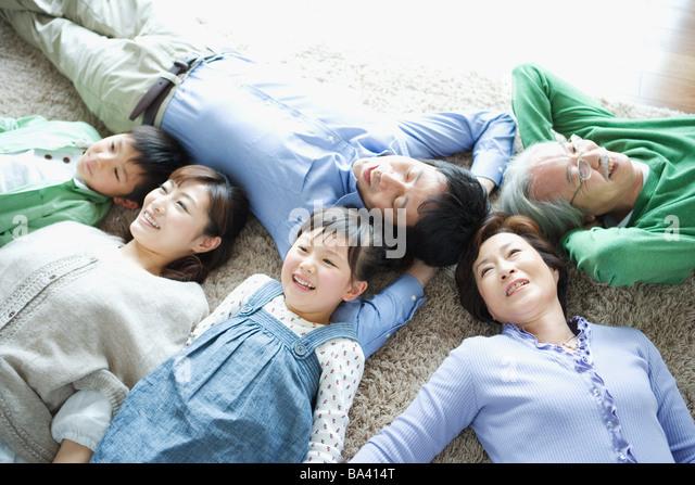 Family lying down on carpet - Stock-Bilder