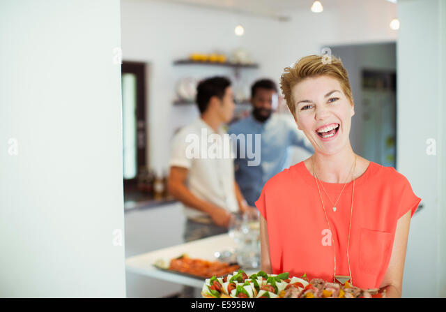 Woman carrying tray of food at party - Stock Image