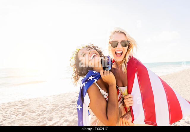 Female friends on beach with American flag - Stock Image