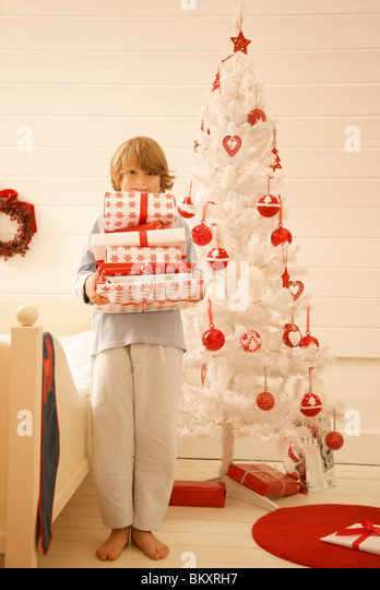 Boy standing by a Christmas tree holding a pile of gifts - Stock Image
