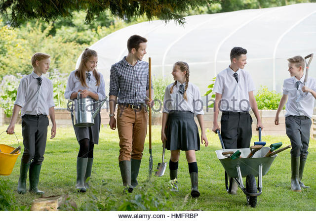 Teacher and middle school students with wheelbarrow learning gardening in garden - Stock-Bilder