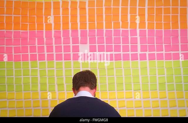Rear View Of Businessman Against Colorful Adhesive Notes On Wall In Office - Stock Image