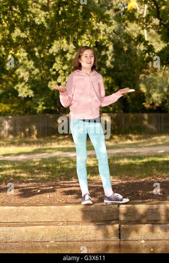 One or the Other. A young girl stands under a tree on the edge of a concrete bank of a creek, trying to make a decision. - Stock Image