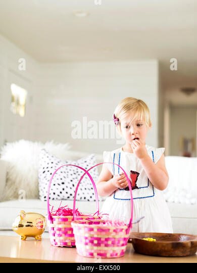 Girl (2-3) eating candy in living room - Stock Image