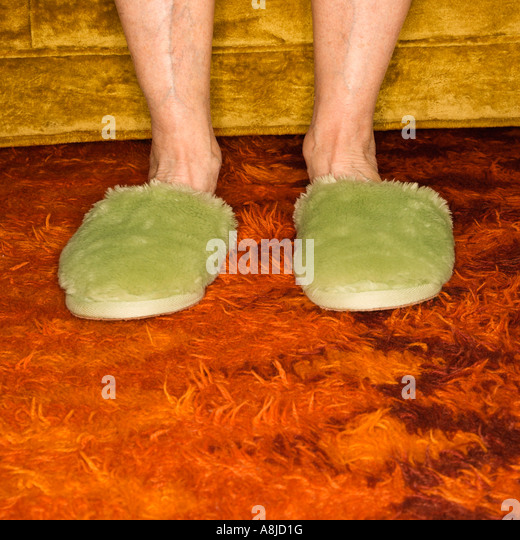Caucasian senior female feet wearing green bedroom slippers on carpet - Stock-Bilder