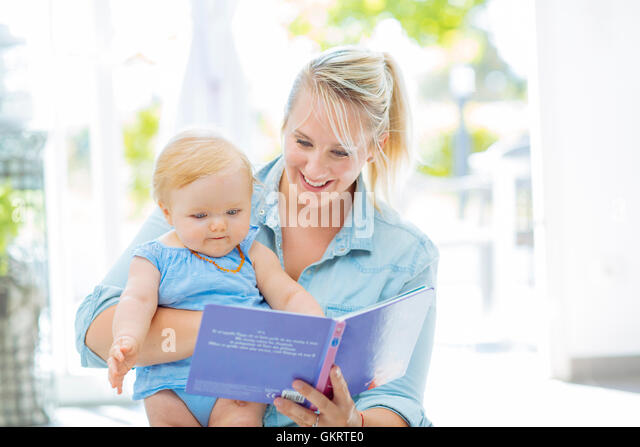 Mom reading a book with her baby girl - Stock Image