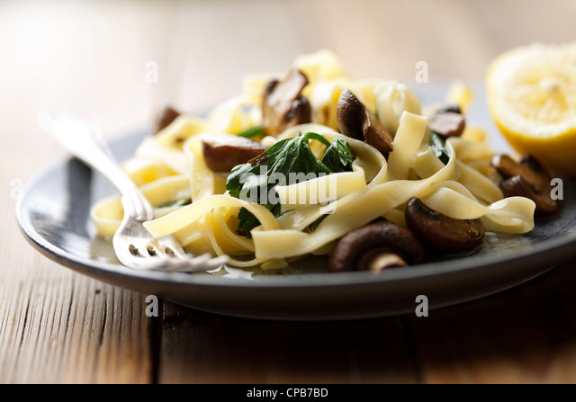 vegetarian dish with tagliatelles, spinach and mushrooms - Stock Image