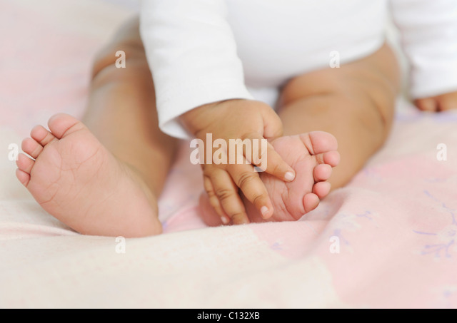 Close up of a baby feeling her feet, Cape Town, South Africa. - Stock Image