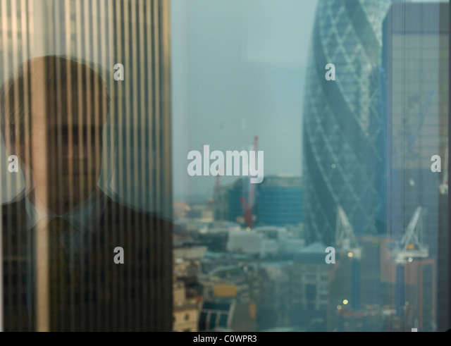 reflection of business man in window with view of London city district in background - Stock Image