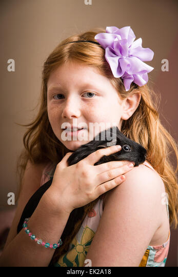 Eight-year old girl holding and cuddling her pet guinea pig on her shoulder - Stock Image