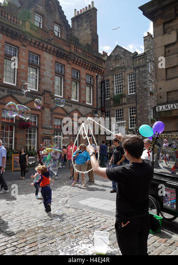 Street Entertainer creating gigantic Bubbles in The Old Town of The City of Edinburgh, Scotland, UK - Stock Image