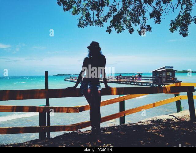 Full Length Of Woman Standing By Railing Against Sky At Beach - Stock Image