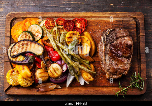 Club Beef steak and Grilled vegetables on cutting board on dark wooden background - Stock Image