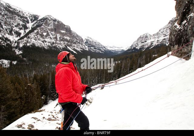 A man belaying an ice climber. - Stock Image
