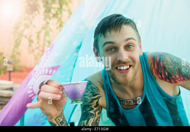 Portrait of young man with teacup in tent - Stock Image