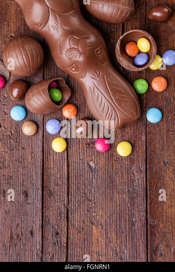 Delicious chocolate easter eggs and sweets on wooden background - Stock-Bilder