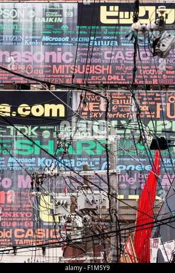 Japan, Osaka. Dotonbori Avenue, telephoto view of wall featuring mass of brand name poster behind electric pylon - Stock Image