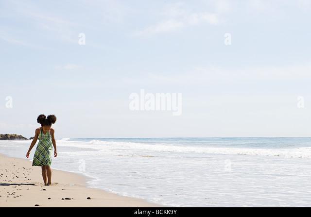 Girl walking on beach alone - Stock Image
