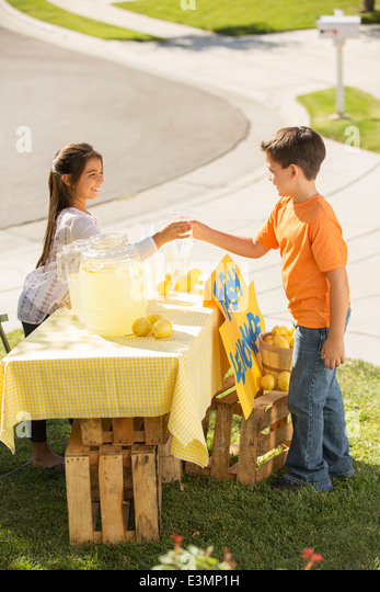 Boy buying lemonade at lemonade stand - Stock Image