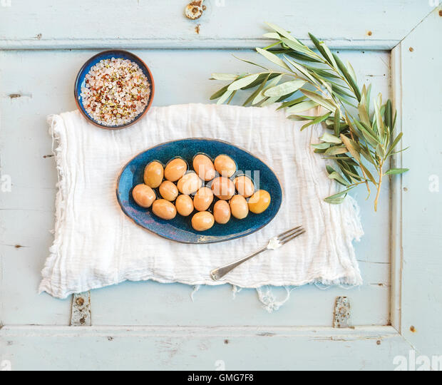 Green big olives in rustic ceramic plate with tree branch and spices - Stock Image