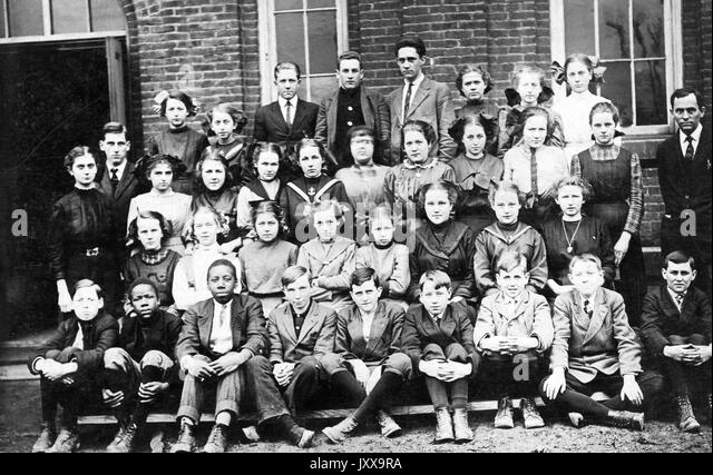 Full length landscape shot of schoolchildren, seated and standing outside building, some African American, one teacher, - Stock Image