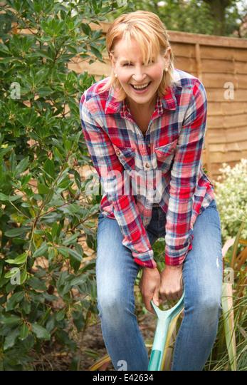 Portrait of mature woman having fun digging garden - Stock Image