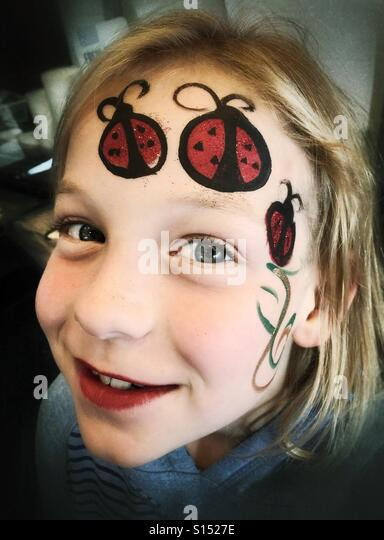 A girl shows off the ladybugs painted onto her face. - Stock Image