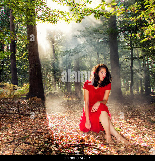 Woman sitting in forest in sunlight - Stock Image