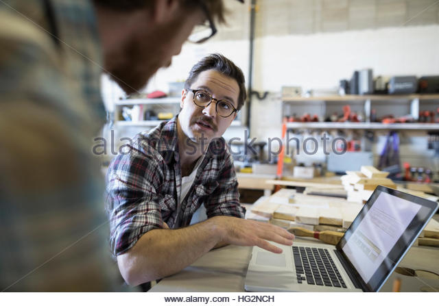 Male carpenters working brainstorming at laptop in workshop - Stock Image