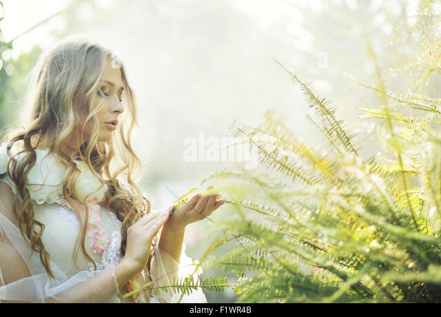 Pretty blonde woman with the green fern - Stock Image
