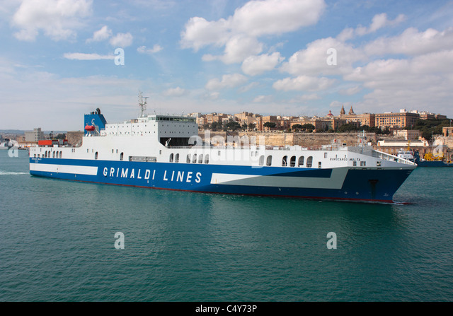 Cargo transport by sea. The Grimaldi Lines ro-ro ship Eurocargo Malta departing from Malta's Grand Harbour - Stock Image
