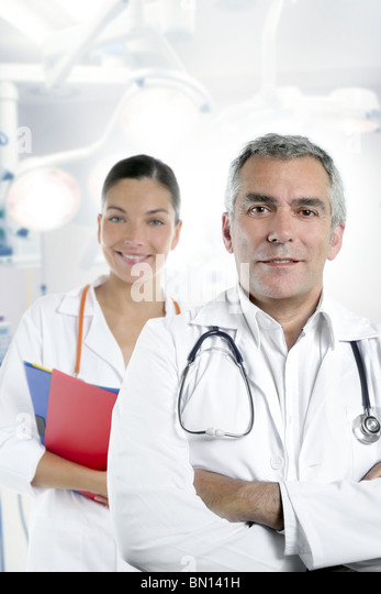 expertise gray hair doctor beautiful nurse in hospital white corridor - Stock Image