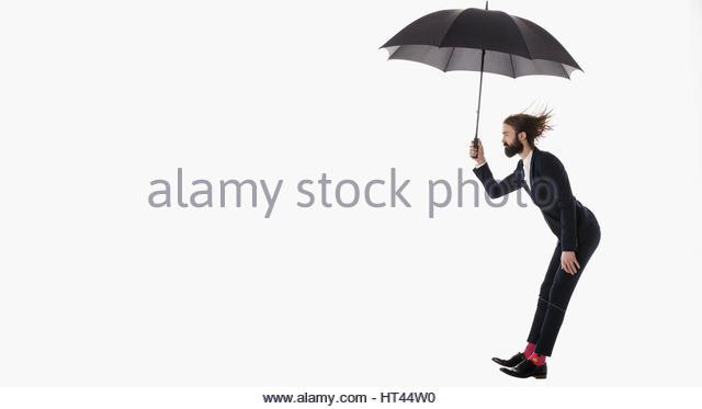 Businessman with umbrella jumping against white background - Stock-Bilder