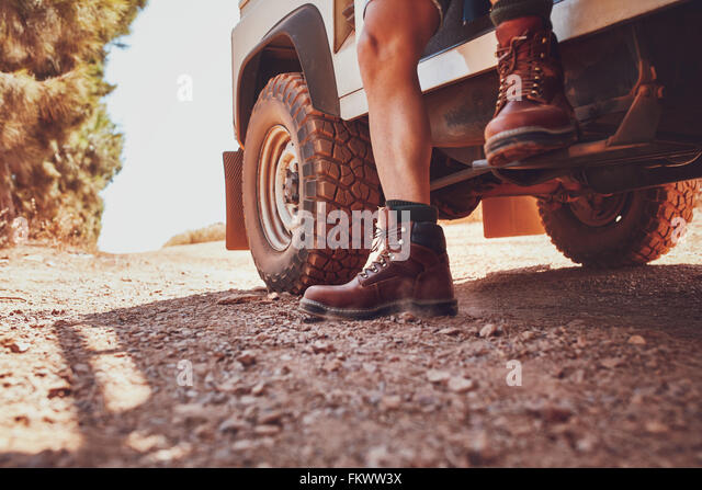 Close up of male leg with leather boot stepping out of a off road vehicle. Car parked on the dirt road in countryside. - Stock Image