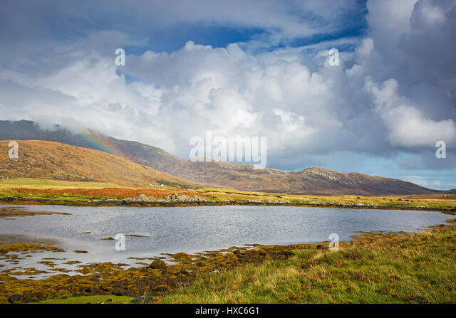 Tranquil view clouds and rainbow over rolling hills beyond lake, Loch Aineort, South Uist, Outer Hebrides - Stock Image